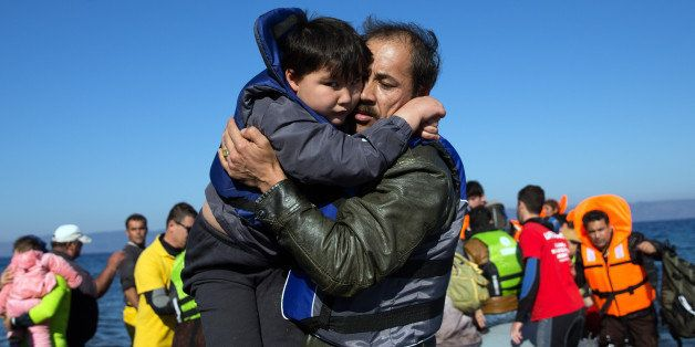 SIKAMINIAS, GREECE - NOVEMBER 12:  A boy is carried ashore as a migrant boat lands after making the crossing from Turkey to t
