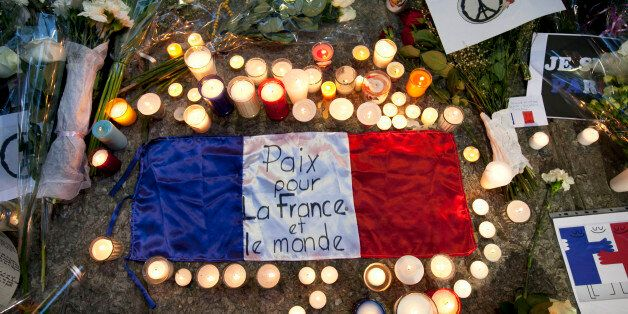 A flag of France is surrounded by candles and flowers outside of the French embassy in Mexico City during a vigil for the vic