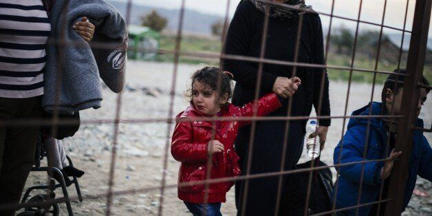? woman and her crying child walk along with other migrants and refugees as they wait to enter a registration camp after cros