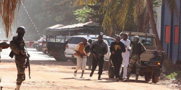 People run to flee from the Radisson Blu Hotel in Bamako, Mali, Friday, Nov. 20, 2015. The company that runs the Radisson Blu