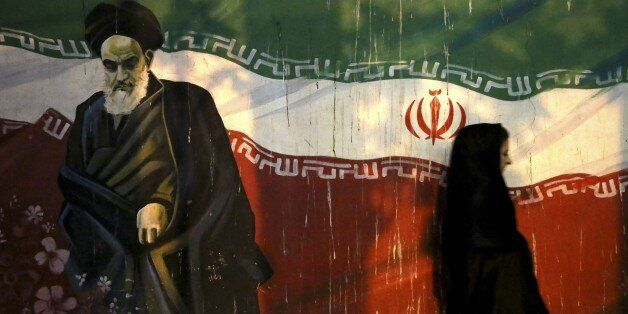 FILE - In this Nov. 2, 2013 file photo, a veiled Iranian woman walks past a mural depicting the late revolutionary founder Ay