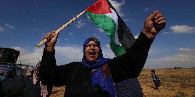 GAZA, Oct. 28, 2015-- A Palestinian woman waves national flag during an anti-Israel protest near the border between Israel an