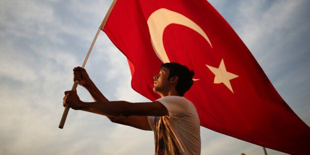 A man waves a national flag as thousands of people march to protest against the deadly attacks on Turkish troops, in Izmir, T