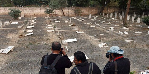 Pakistani news photographers take pictures of desecrated graves at the minority Ahmadi sect graveyard in Lahore on December 3