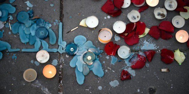Candles and flower petals are left at the Place de la Republique in the French capital Paris, on November 23, 2015 as people