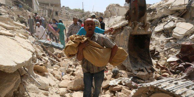 A Syrian man carries a body after it was removed from the rubble of buildings following a reported barrel bomb attack by gove