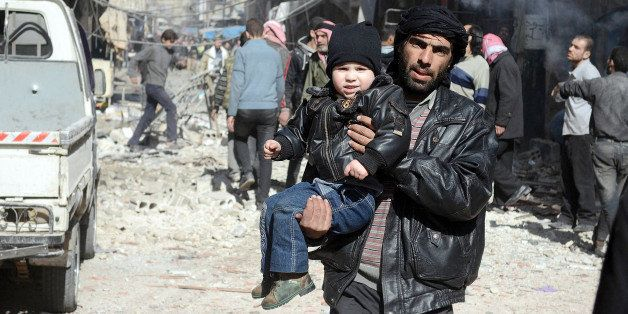 DOUMA, SYRIA - FEBRUARY 02: A Syrian man takes his son away after Syrian regime's air forces' air attack on East Ghouta regio