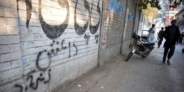 A Pakistani pedestrian walks past wall graffiti (bottom) which reads Daesh, the arabic acronym for Islamic State (IS), in Pes