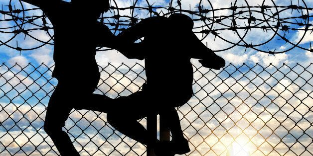 Concept of the refugees. Silhouette of refugees crossing the fence with barbed wire against the evening sky and the city in t