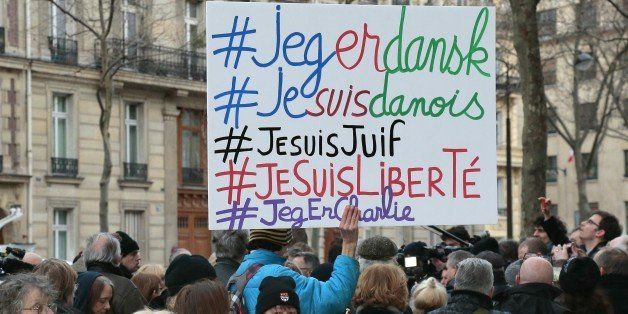 A man holds a placard with the hashtags 'I am Danish, I am Jewish, I am Freedom'  next to a woman holding a Danish flag  outs
