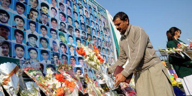 RAWALPINDI, PAKISTAN - DECEMBER 16: A Pakistani man lays flowers at a makeshift memorial for the victims of Taliban's deadlie