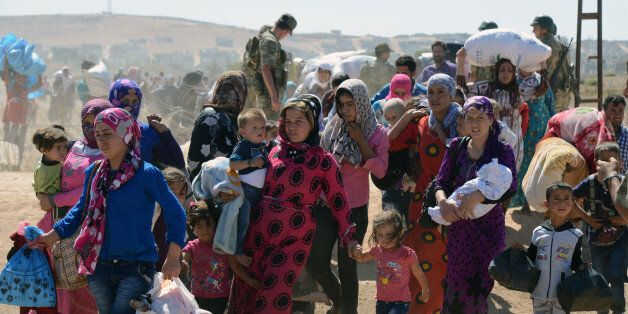 Syrian refugee women and children gather at the border in Suruc, Turkey, Saturday, Sept. 20, 2014. TSeveral thousand Syrians,