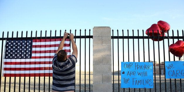 SAN BERNARDINO, CA - DECEMBER 04:  Ernesto Vasquez hangs an American flag  at a makeshift memorial near the Inland Regional C
