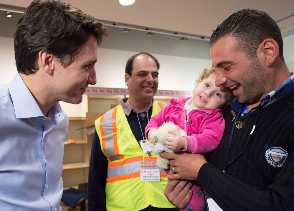 Prime Minister Justin Trudeau greets 16-month-old Madeleine Jamkossian and her father Kevork Jamkossian, refugees fleeing the