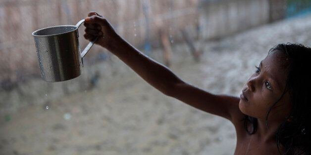 SHYAMNAGAR, SATKHIRA, KHULNA, BANGLADESH - 2015/08/28: Rani is 9 years old girl, collects rain water for drinking. Rainwater
