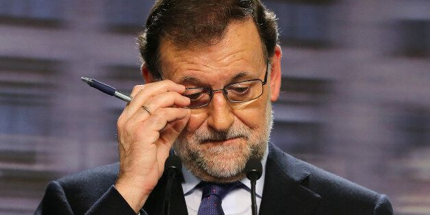 Spanish incumbent Prime Minister Mariano Rajoy (C) touches his glasses during a press conference after the national executive