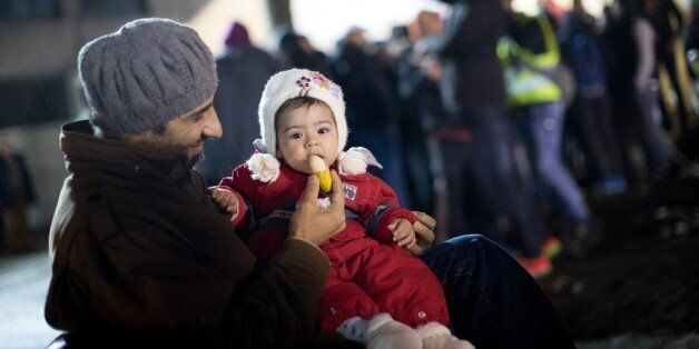 A man from Syria feeds his daughter as asylum seekers line up in front of the State Office of Health and Social Affairs (LAGe