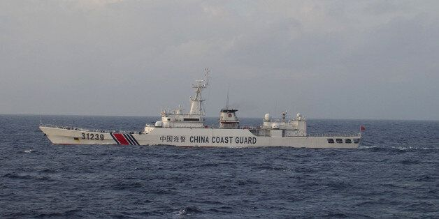 In this photo provided by Japan Coast Guard, an armed Chinese coast guard ship sails in the water near islands, known as the