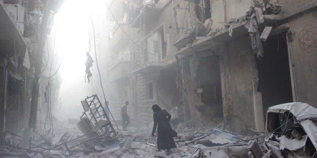 A Syrian woman makes her way through debris following an air strike by government forces in the northern city of Aleppo on Ju