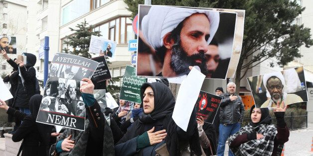 Iranian and Turkish demonstrators hold pictures of Shiite cleric Sheikh Nimr al-Nimr as they protest outside the Saudi Embass