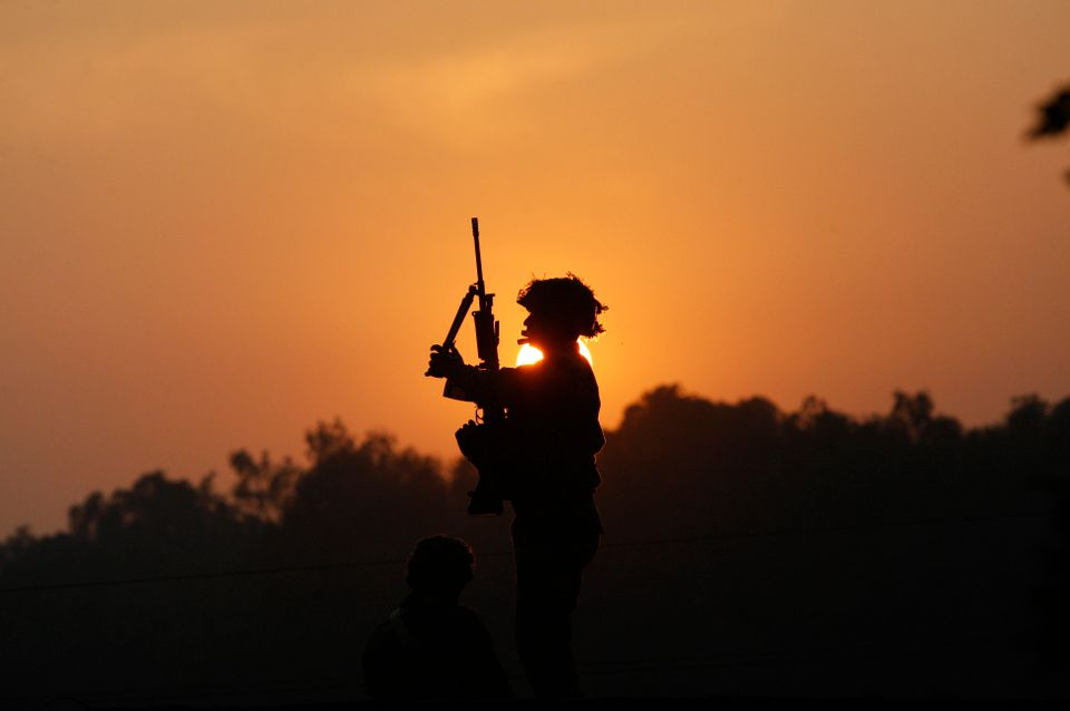 An Indian army soldier is silhouetted against the setting sun as he stands guard next to his colleague, sitting on the roof t