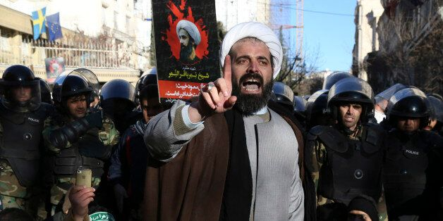 Surrounded by policemen, a Muslim cleric addresses a crowd during a demonstration to protest the execution of Saudi Shiite Sh