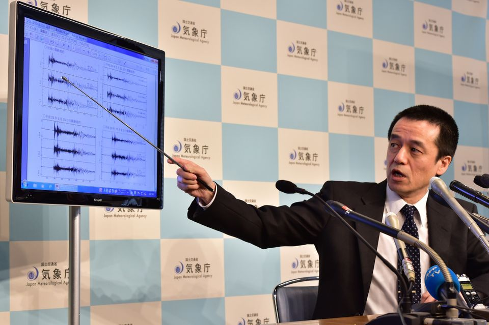 Japan's meteorological agency officer Yohei Hasegawa displays a chart showing seismic activity, (at L top is today's observat