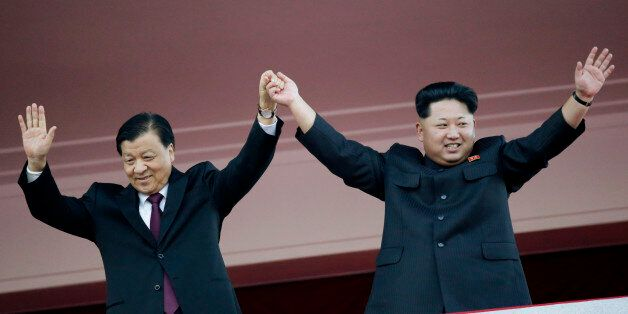 In this Oct. 10, 2015, file photo, North Korean leader Kim Jong Un, right, joins hands and waves with visiting Chinese offici