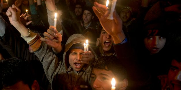 Kashmiri Shiite Muslim boys shout slogans as they hold candles during a protest against Saudi Arabia in Srinagar, Indian cont