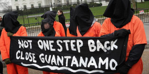 WASHINGTON, DC - JANUARY 08:  Demonstrators with the group Witness Against Torture dress in orange jumpsuits and wear black h