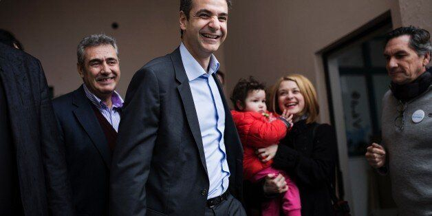 Candidate for the leadership of Greece's conservative New Democracy party, Kyriakos Mitsotakis (C) leaves after casting his b