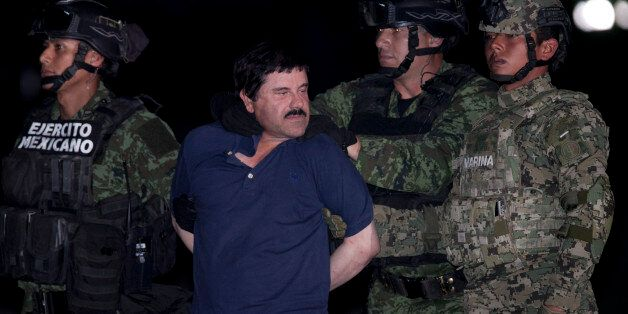 """Joaquin """"El Chapo"""" Guzman is made to face the press as he is escorted to a helicopter in handcuffs by Mexican soldiers and ma"""