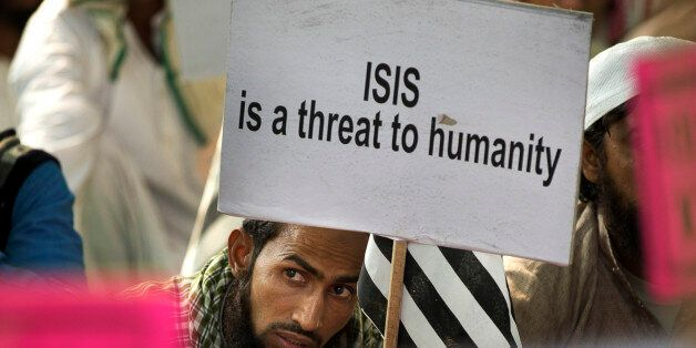 An Indian Muslim man holds a banner during a protest against ISIS, an Islamic State group, and Friday's Paris attacks, in New
