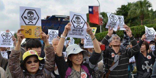Local residents display signs demanding better food safety during a demonstration in Taipei on December 12, 2015.  Hundreds o