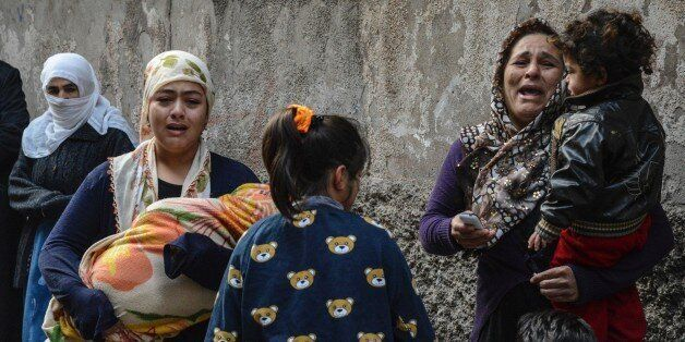 Women react after a mortar hit a house during clashes with Turkish police at the Sur district in Diyarbakir, southeastern Tur