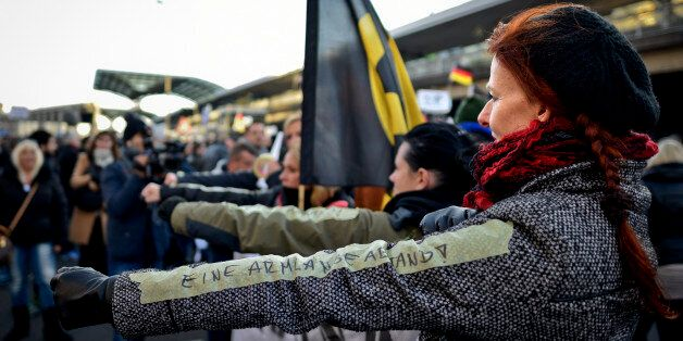 COLOGNE, GERMANY - JANUARY 09:  A German far-right supporter demonstrates with a sticker reading 'an arm-length distance' ref