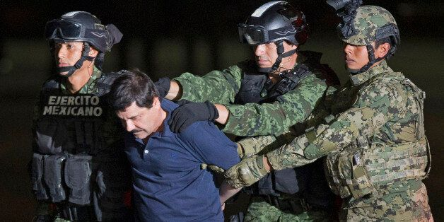 """Mexican army soldiers escort drug lord Joaquin """"El Chapo"""" Guzman to a helicopter to be transported to a maximum security pris"""
