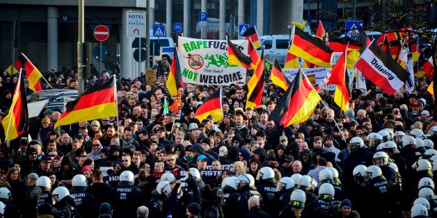 COLOGNE, GERMANY - JANUARY 09:  Protesters wave German flags, alongside a banner saying 'Rapefugees Not Welcome' as supporter