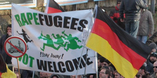 """Right-wing demonstrators hold a sign """"Rapefugees not welcome - !Stay away!"""" and a sign with a crossed out mosque as they marc"""