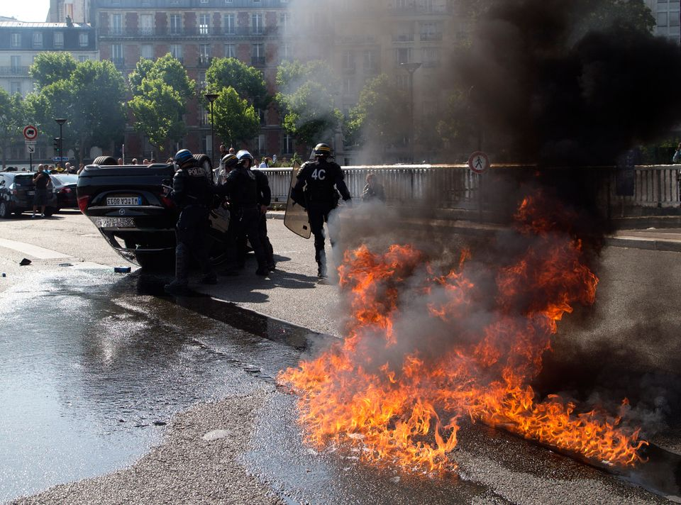 Riot police officers stand by an overthrown car during a taxi drivers demonstration, Thursday, June 25, 2015 in Paris, France
