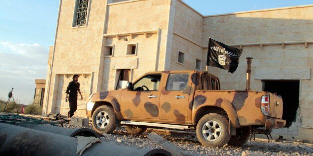 An opposition fighter walks near a vehicle flying a black Jihadist flag with Islamic writing on it proclaiming in Arabic that