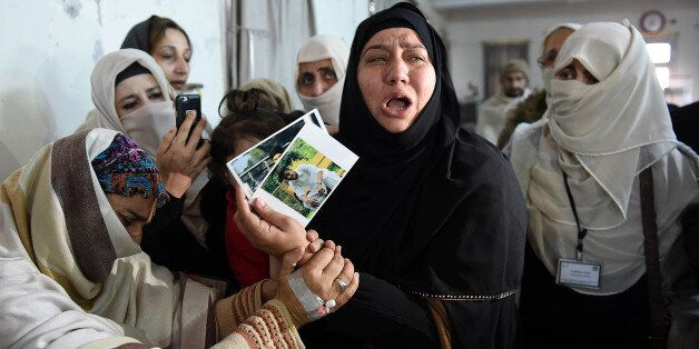 TOPSHOT - A relative of a 2014 Peshawar school attack victim shows her son's pictures to a student victim (L) of the Bacha Kh