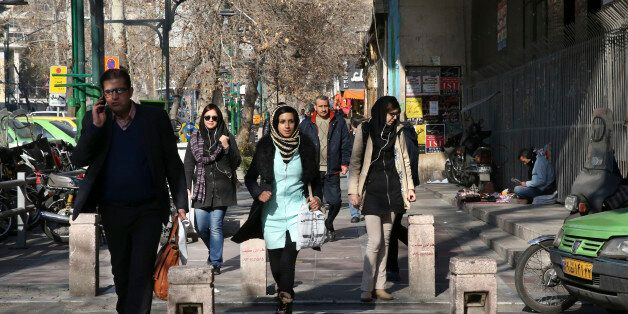Pedestrians cross a street in central Tehran, Iran, Saturday, Jan. 16, 2016. The end of Western sanctions against Iran loomed
