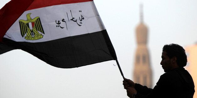 An Egyptian youth waves the national flag with slogan in Arabic that reads. '25th of January, Day of the Freedom'  following