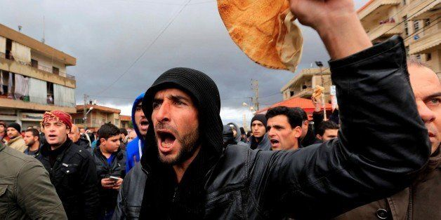 BEQAA, LEBANON - JANUARY 8: Demonstrators holding breads chant slogans against Syrian regime and Hezbollah, during a protest