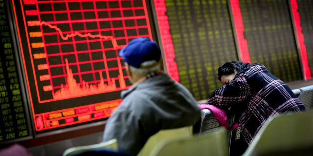 A woman takes a nap as a man looks at an electronic board displaying stock prices at a brokerage house in Beijing, Monday, Ja