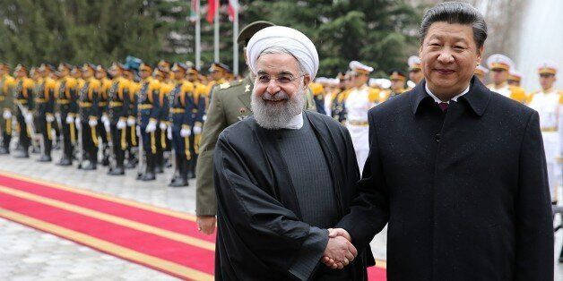 TEHRAN, IRAN - JANUARY 23 : Chinese President Xi Jinping (R) and Iranian President Hassan Rouhani (L) shake hands during an o