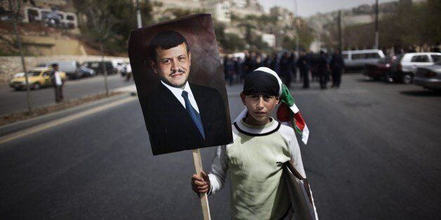 A young Jordanian parades with a portrait of the King Abdullah II in front of policemen during a pro government demonstration