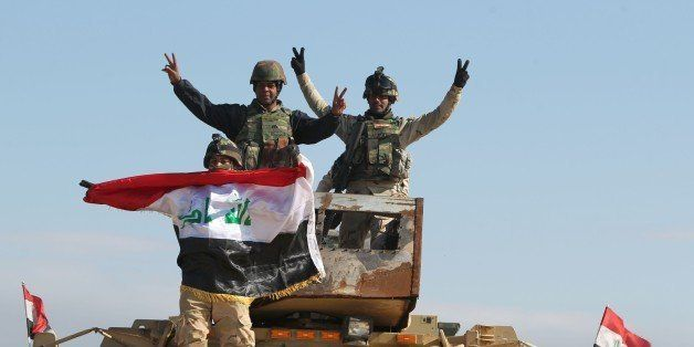 Iraqi soldiers wave their national flag after a live-fire exercise under the surveillance of US-led coalition forces at Basma