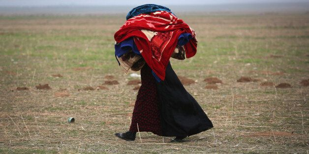 SINJAR, IRAQ - NOVEMBER 16:  A woman carries blankets into a Kurdish-controlled area after fleeing her ISIL or Daesh-held fro